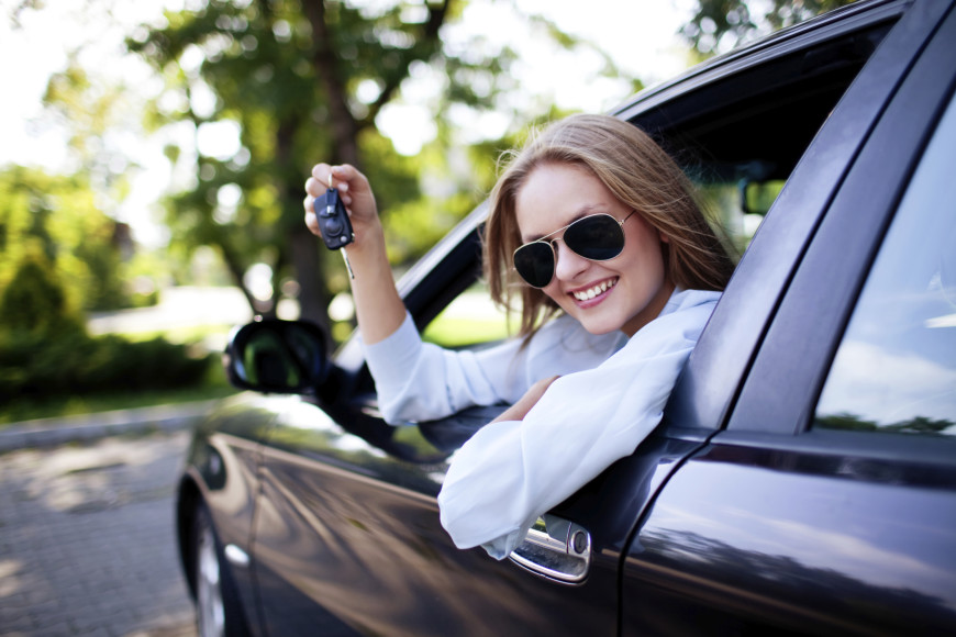 Woman leaning out of driver's window smiling and holding car keys