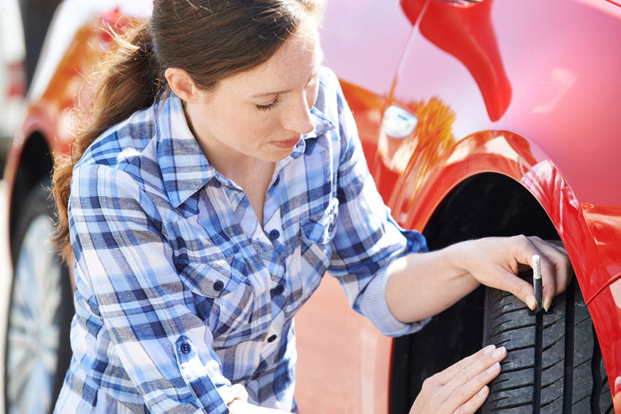 woman using gauge to check her car tires