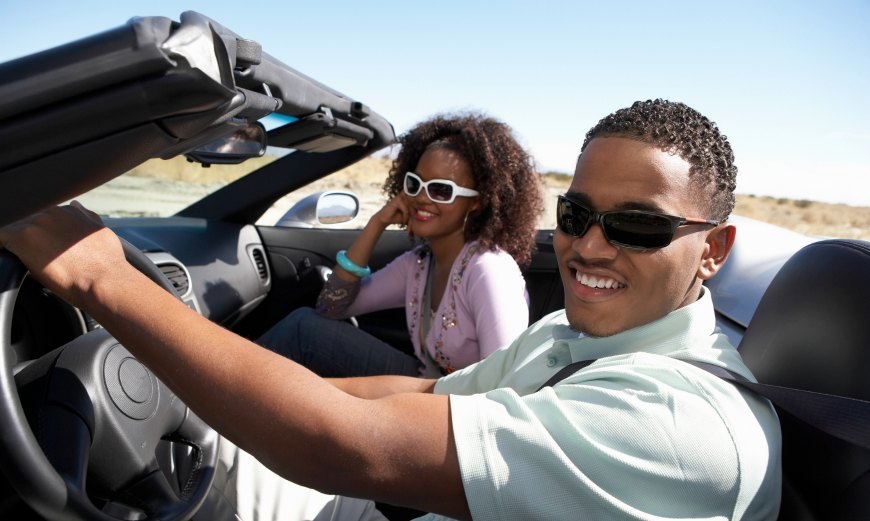 Couple driving convertible on sunny day