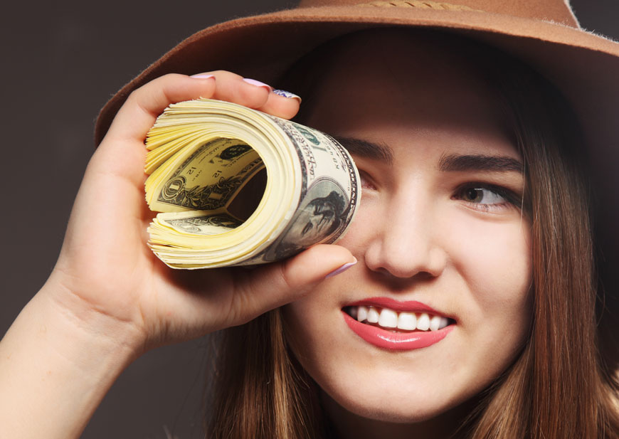 Woman looking through rolled stack of U.S. paper money