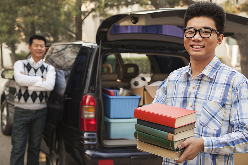 Father and son packing up car for college