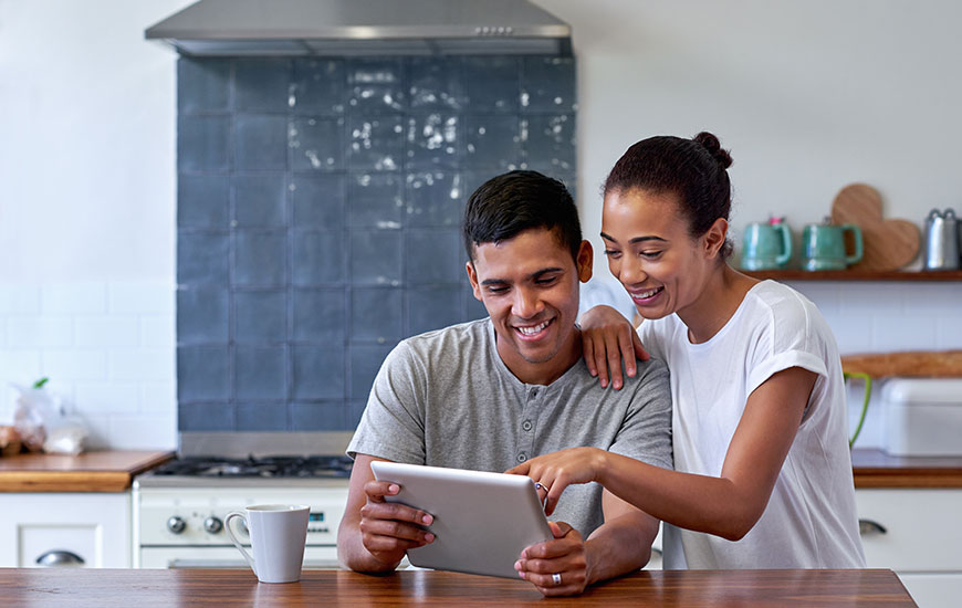 man and woman at kitchen table looking at a tablet