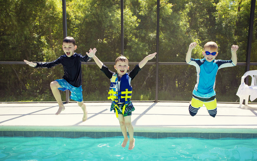 three young children jumping into a pool