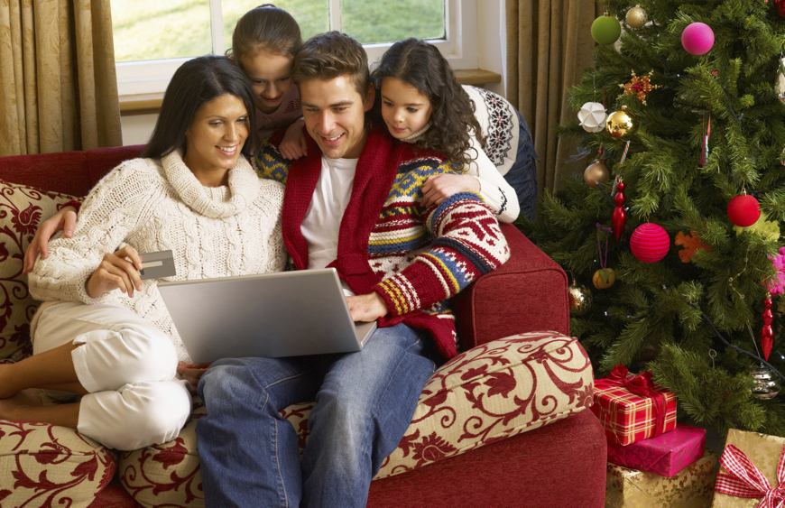 family with laptop and credit card sitting by Christmas tree