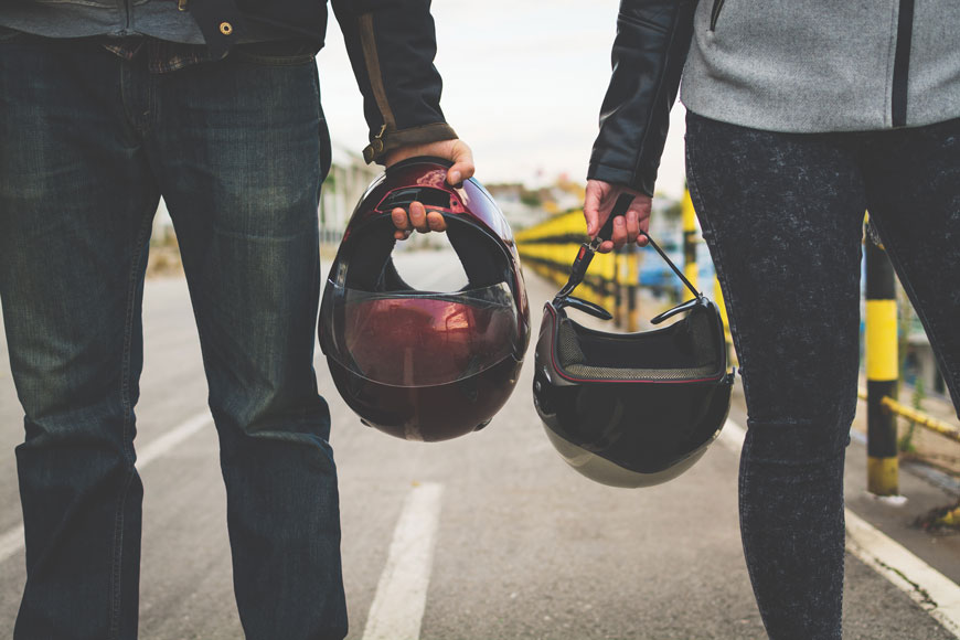Two people standing on a road holding motorcycle helmets