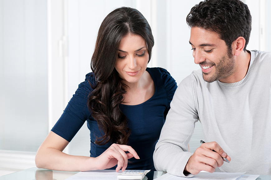 Man and woman looking over paperwork with calculator