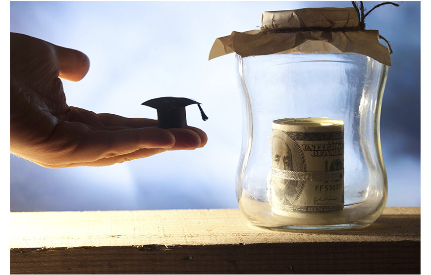 Image of hand holding small graduation hat in front of jar of money