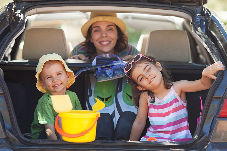 woman with two young children in back of car ready for the beach