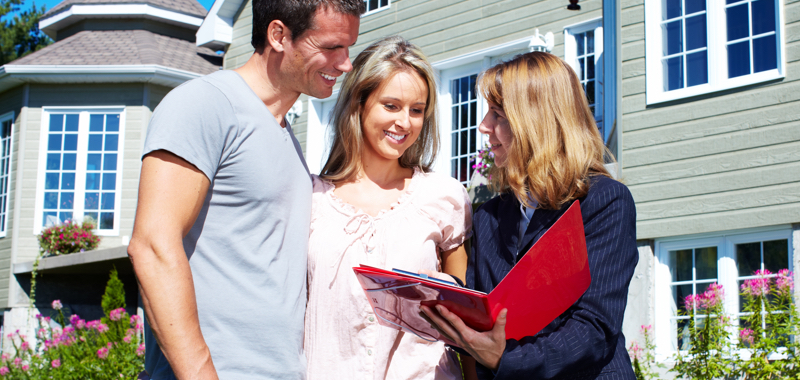 couple in front of home with REALTOR®